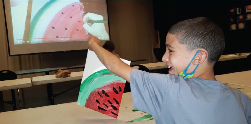 Boy holding a painting of a watermelon at the Boys & Girls Club of Geneva